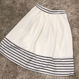 Pleated white skirt with striped trim